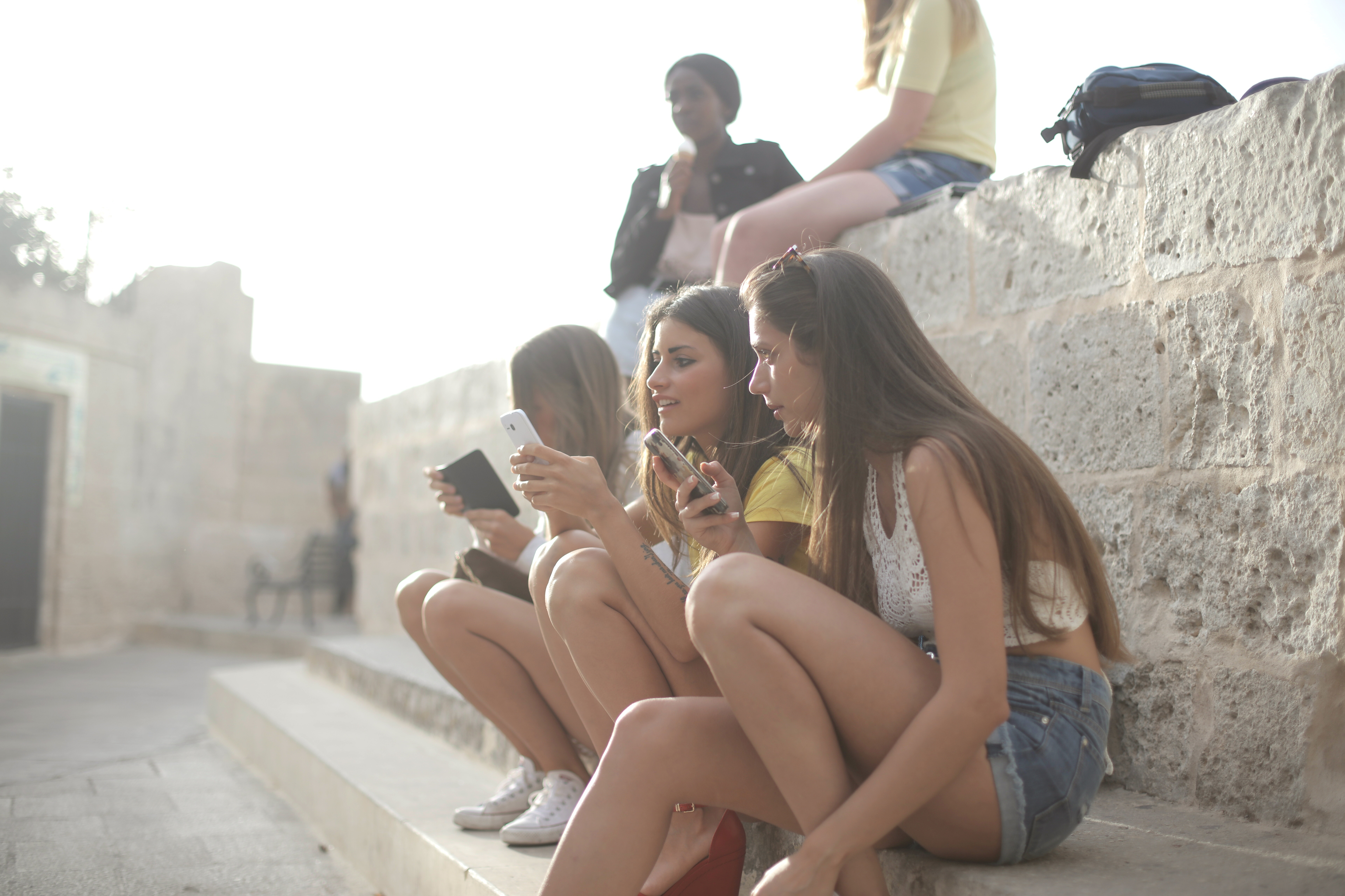 3-women-sitting-on-concrete-steps-3989936