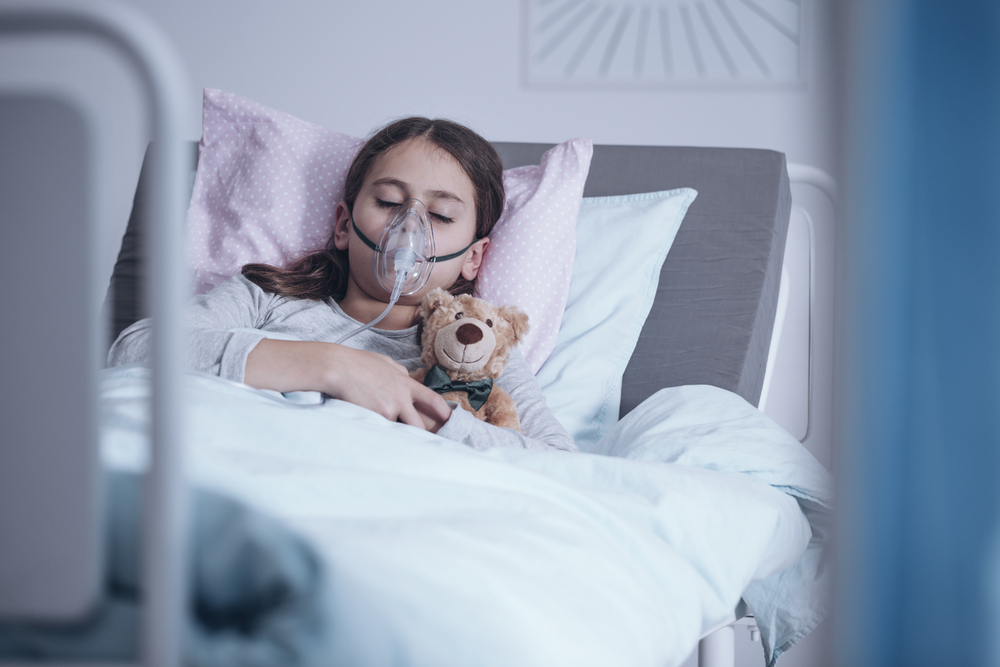 Sick girl with oxygen mask sleeping in a hospital bed with teddy