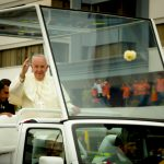 Pope Francis standing on popemobile and waving